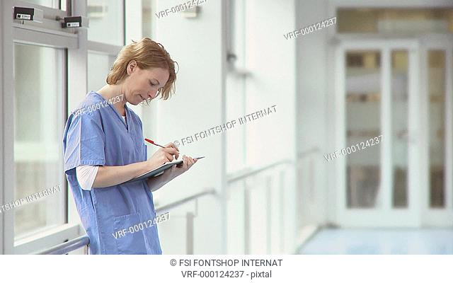 Medium lockdown shot of a nurse writing on a medical chart as two doctors are approaching