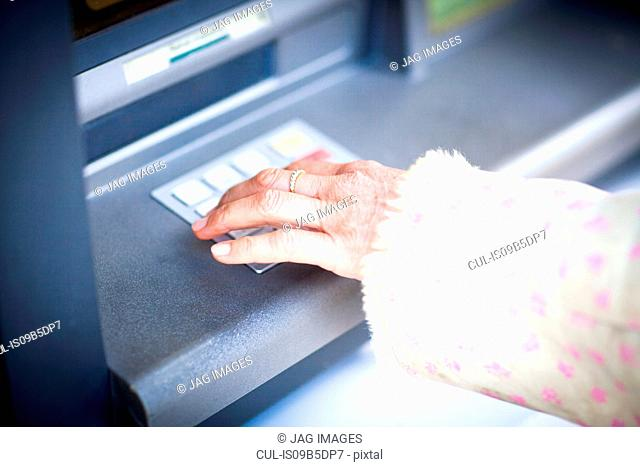 Hand of woman pressing keyboard at local french cash machine