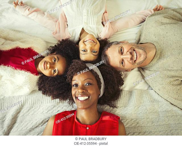 Overhead portrait smiling multi-ethnic young family laying on bed