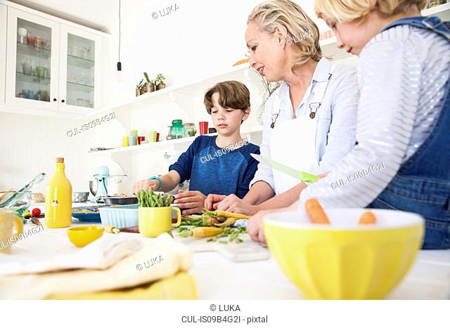 Mature woman preparing vegetables at kitchen table with son and daughter