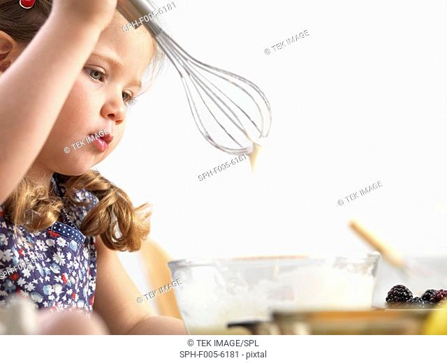MODEL RELEASED. Young girl baking. Three year old girl baking