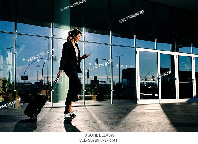 Businesswoman with wheeled luggage passing glass building, Malpensa, Milan