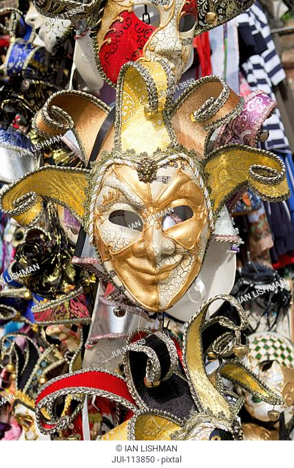 Ornate jester Venetian mask for Venice Carnival hanging in market stall, Italy
