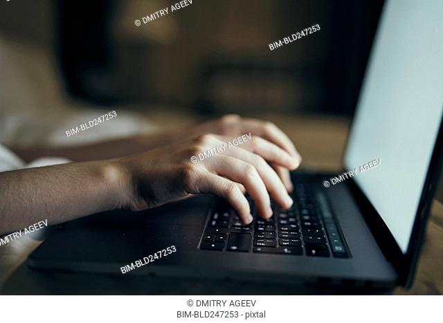 Hands of Caucasian woman typing on laptop in bed