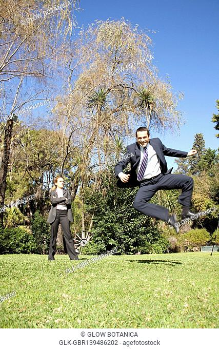 Businessman jumping in a park with a businesswoman