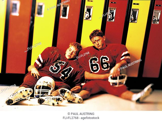 Dejected football players sitting in front of lockers