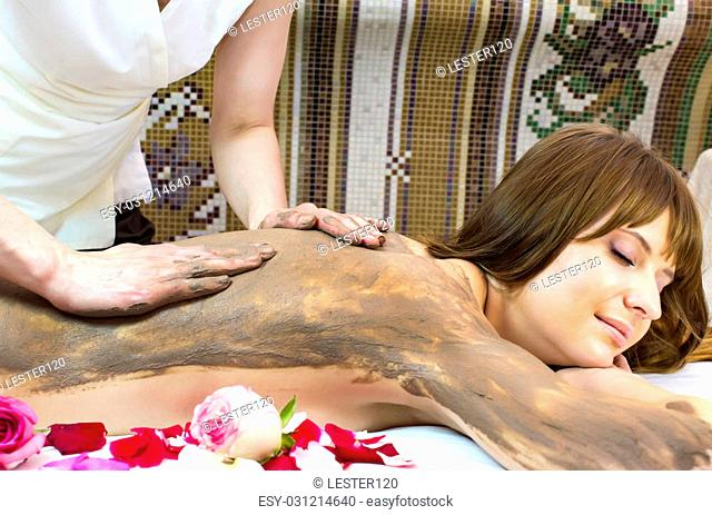 Young girl doing a clay massage procedure
