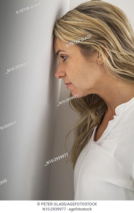 Young blonde woman's head leaning against a wall