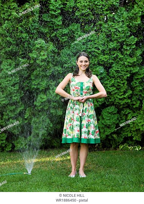 woman in a dress standing in the sprinklers