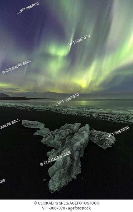 Northen Lights over block of ice in Jokulsarlon Glacier Lagoon, Austurland, Eastern Iceland, Iceland, Europe