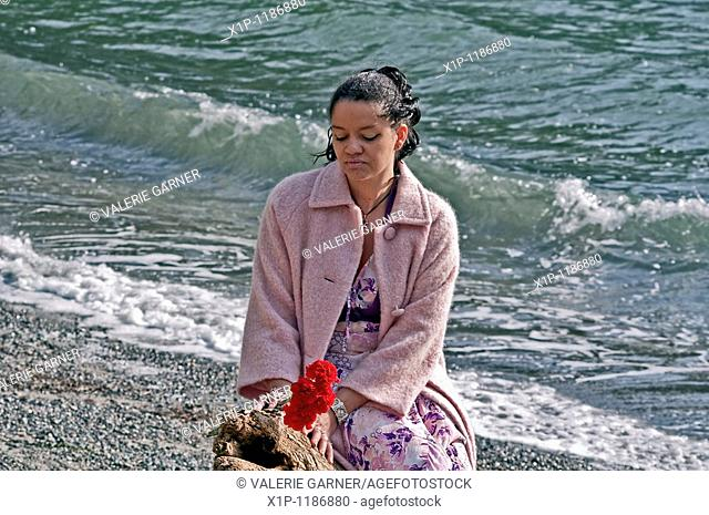 This pretty multi racial woman in her thirties is wearing a pink coat and holding red carnation flowers at the beach Her mood is one of quiet reflection and...