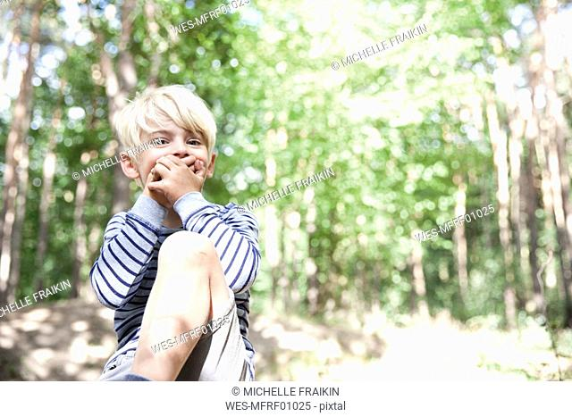 Boy in forest covering his mouth with his hands