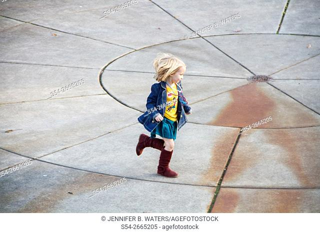 A little girl plays outdoors in Bothell, Washington, USA