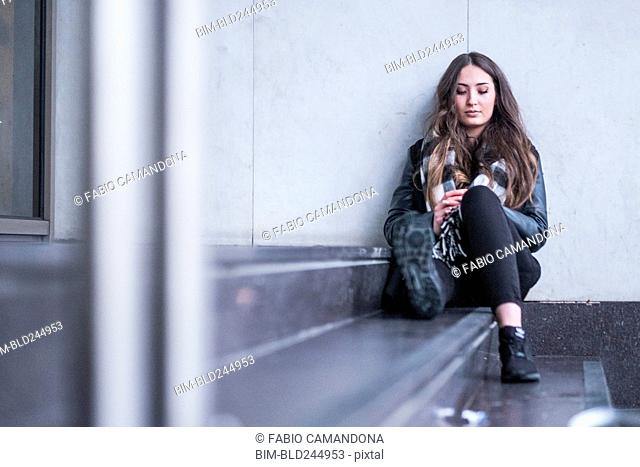 Pensive Caucasian woman sitting on staircase