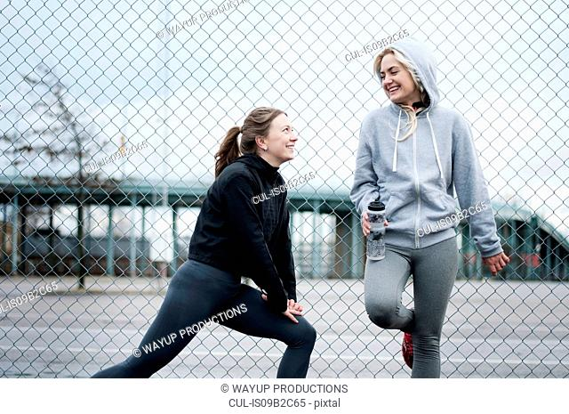 Two female running friends warming up by wire fence