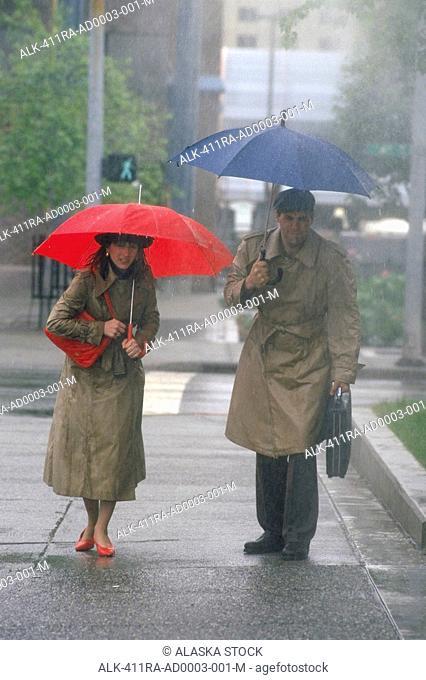 Businesspeople w/ umbrella in rainstorm Anchorage SC Alaska summer portrait