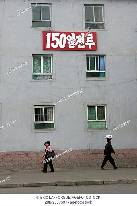 People Passing By A Building, North Korea
