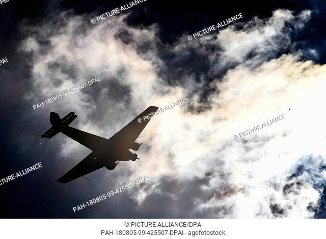 FILED - ILLUSTRATION - 22 May 2017, Germany, Cologne: A historical Junkers Ju 52 plane flies over Cologne against the light