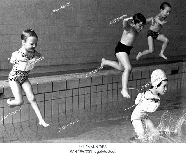 Disabled children, some wearing flotation devices - some don't, jump courageously into the water in a photograph taken in May 1968