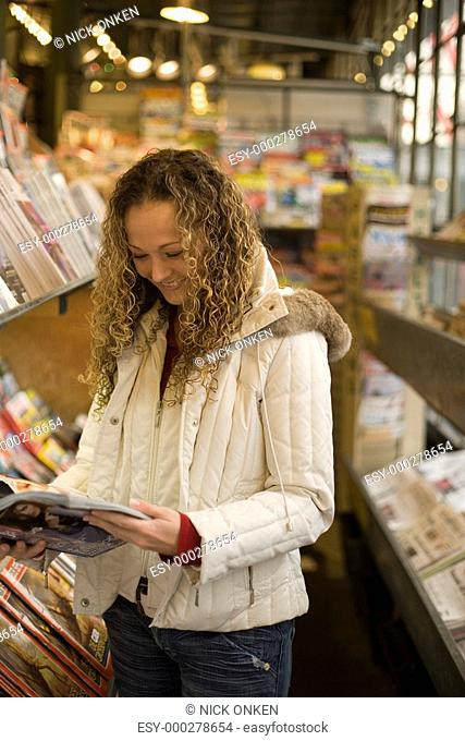 Young woman reading magazine in news stand