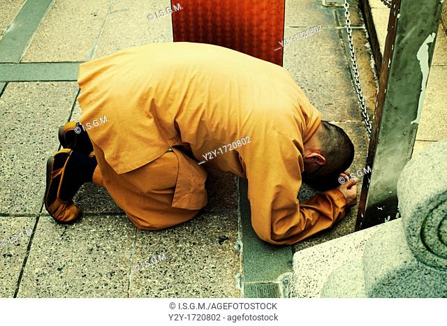 Buddhist shaolin monk praying at Temple of Lantau in China