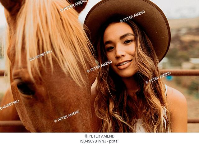 Young woman in felt hat next to horse, close up portrait, Jalama, California, USA
