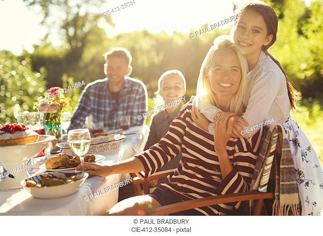Portrait smiling affectionate mother and daughter hugging at sunny garden party patio table