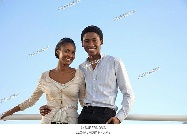 Work colleagues standing arm in arm on office balcony, Cape Town, Western Cape Province, South Africa