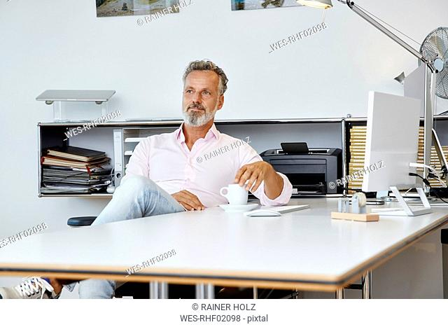 Businessman sitting at desk in office thinking