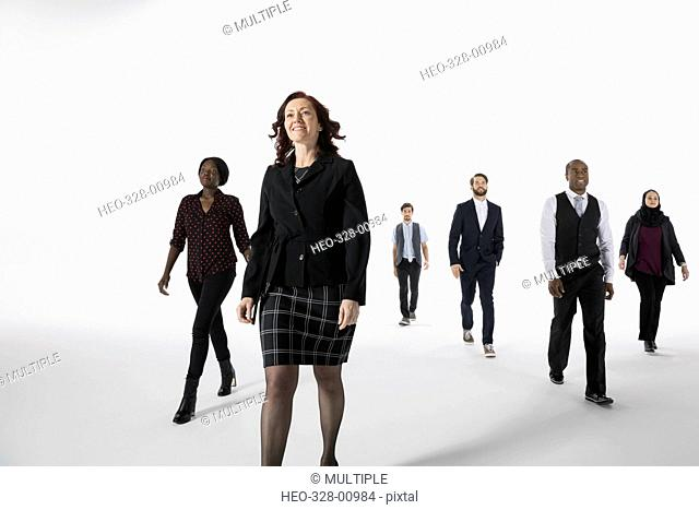 Confident businesswoman leading business people against white background
