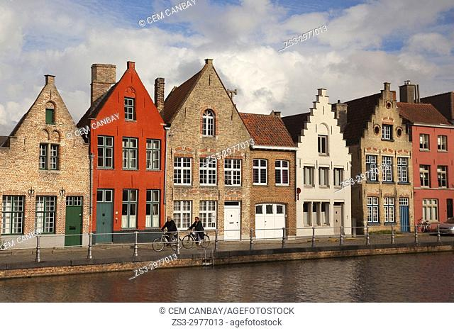 Cyclists in front of the the colorful traditional houses by the canal in the city centre, Bruges, West Flanders, Belgium, Europe