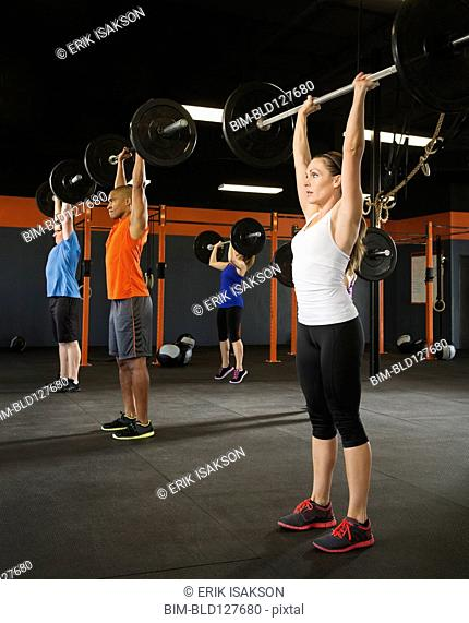 People lifting weights in gym