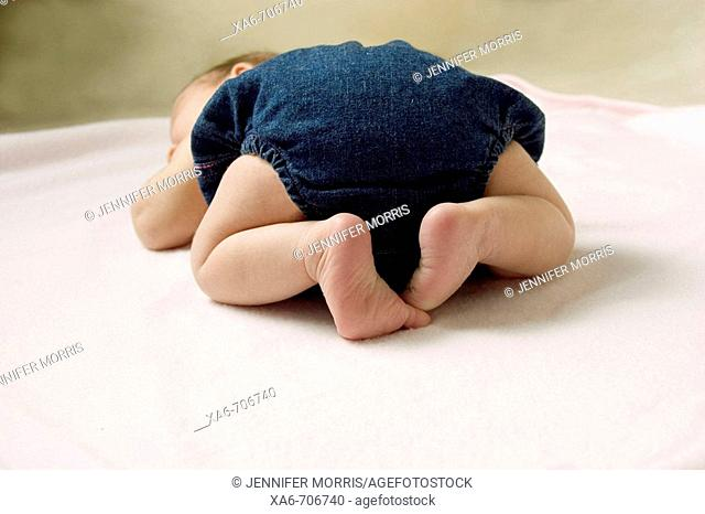 A newborn baby wearing a denim diaper cover lies sleeping on her front on a pink blanket