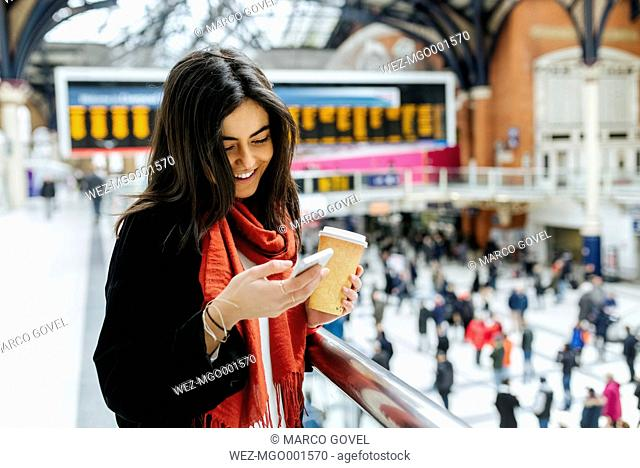 UK, London, Young woman using mobile phone at train station