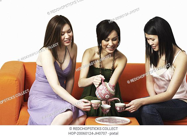 Three young women sitting on a couch with tea cups