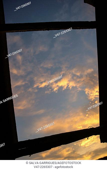 Picture of a sky at sunset seen from a window frame