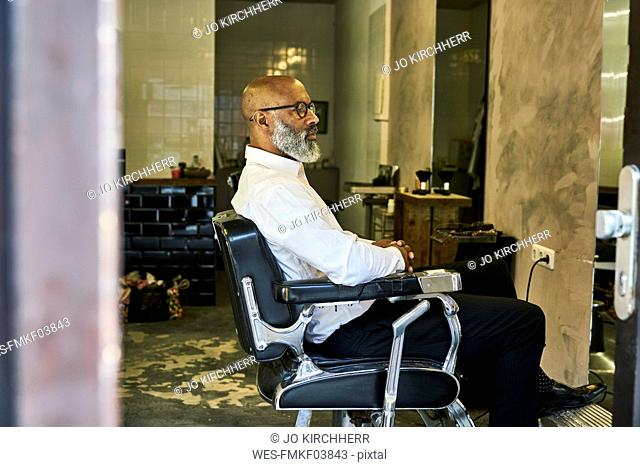 Mature businessman reading smartphone messages