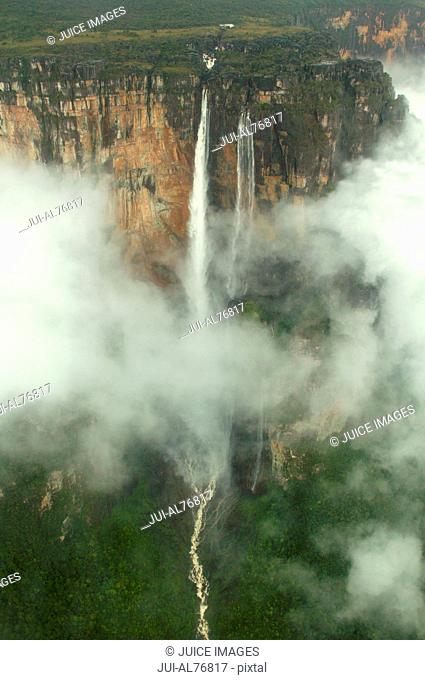 Aerial view of cliffs and a waterfall cloaked in fog, Angel Falls, Canaima National Park, Venezuela