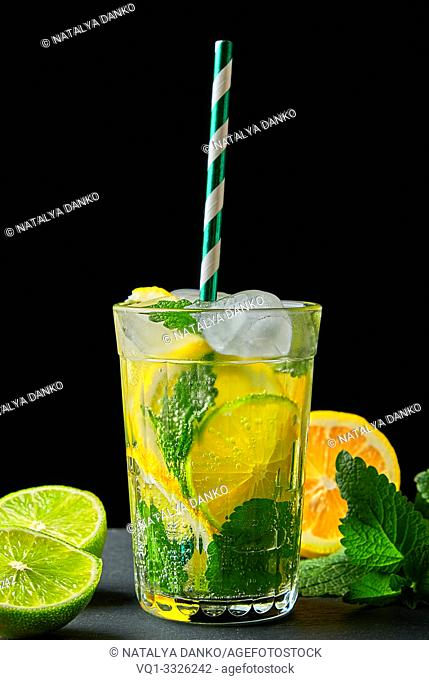 refreshing drink lemonade with lemons, mint leaves, ice cubes and lime in a glass on a black background