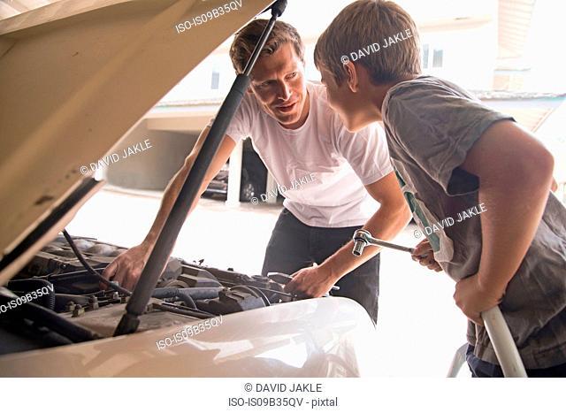 Father explaining car maintenance to son under car hood