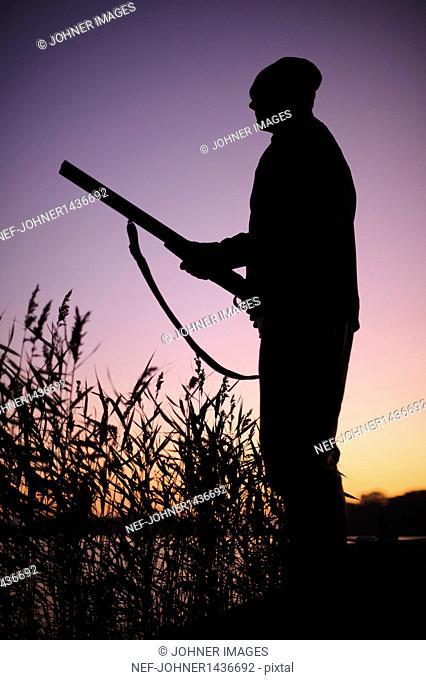Hunter holding gun at lake at dusk