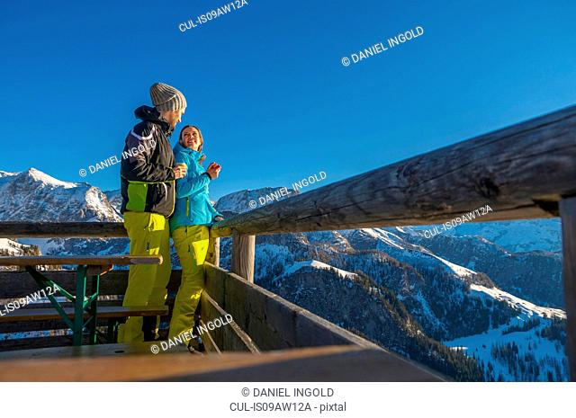 Couple wearing ski suit on viewing platform in mountains smiling, Jenner, Berchtesgadener, Germany