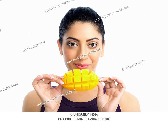 Portrait of a woman holding a slice of mango