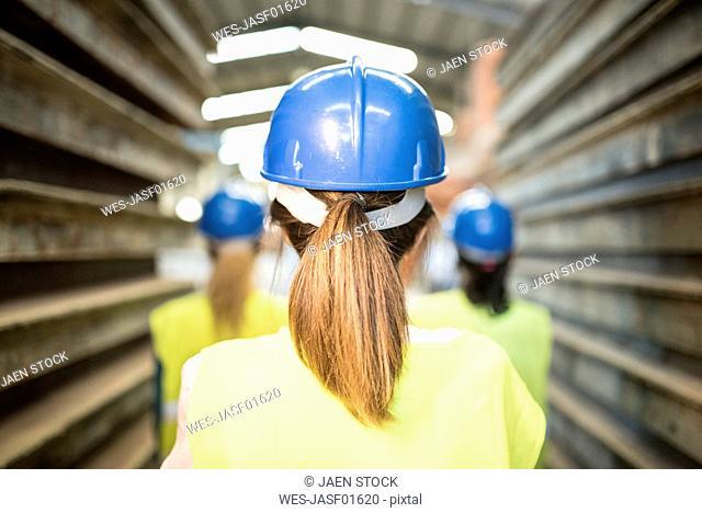 Three industry workers standing by steel girders, rear view