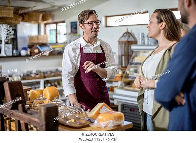 Grocer presenting cheese in a farm shop