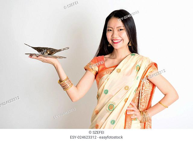 Indian housewife hand holding empty plate ready for food standing on plain background