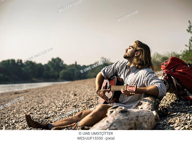 Young man sitting at the riverside playing guitar