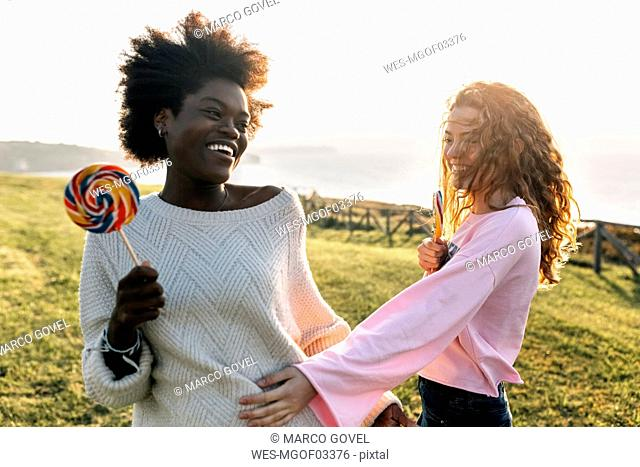 Two best friends having fun with lollipops outdoors