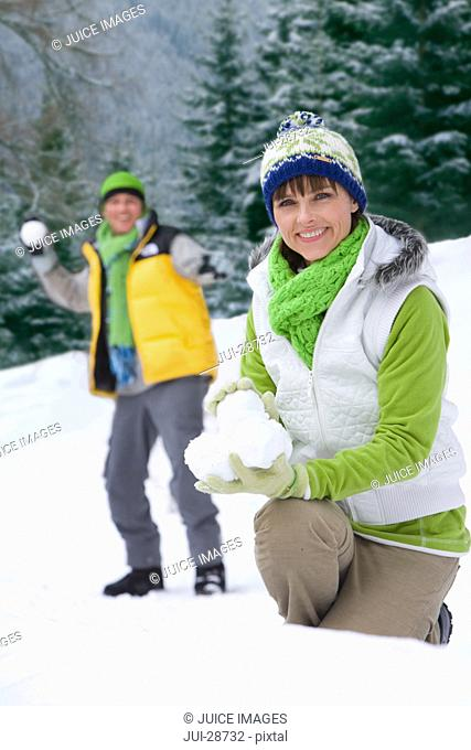 Smiling couple having snowball fight in woods together