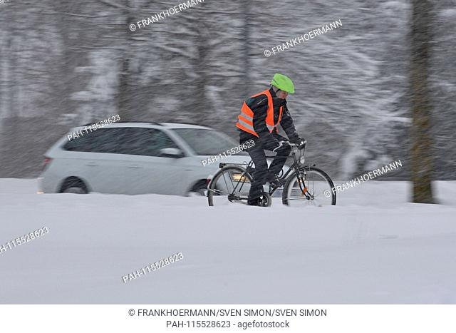 Snow chaos on the streets of Bavaria - probably the one who comes by bike to his place of work, like this cyclist with signal vest driving on a snowy